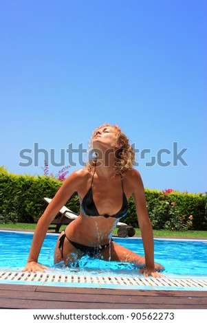 Beautiful young woman at the swimming pool in her private villa