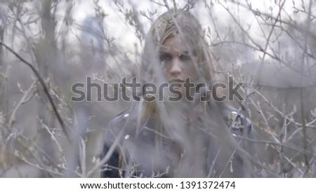 Beautiful young woman behind the bushes in autumn. Action. A woman from behind the bushes looking at the camera