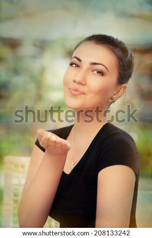 Beautiful Young Woman Blowing Kisses - Colorful portrait of a young woman blowing kisses at the camera