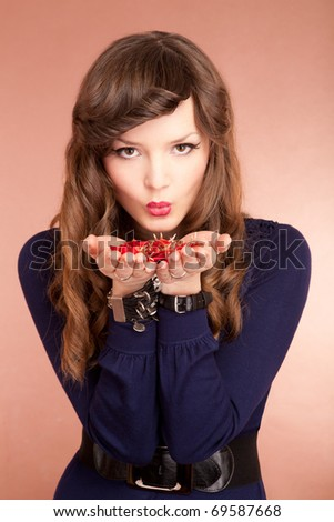 Beautiful young woman blowing on flower petals - stock photo