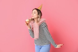 Beautiful young woman blowing out candle on birthday cupcake against color background