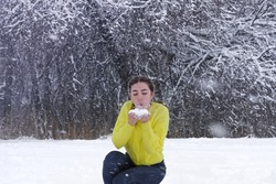 Beautiful young woman blows snow from hands in winter forest. Powder snowflakes fly up. Joyful lady in bright yellow jacket against background of  white snowdrift.