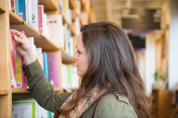 Beautiful young woman browsing and reading in bookstore or library