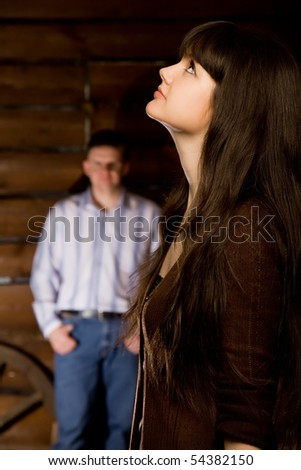 beautiful young woman brunette and young man in wooden log hut, woman standing near wall on background, focus on woman, looking upwards