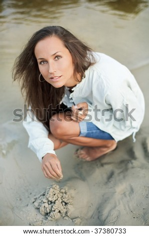Beautiful young woman building sand castle on the lake coast