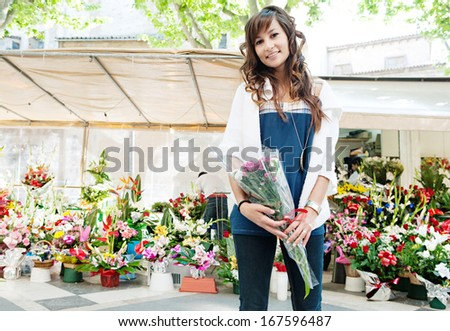 Beautiful young woman buying and holding a small bouquet of fresh flowers from a city floral market stall with colorful arrangements of fresh flowers, during a sunny day outdoors.