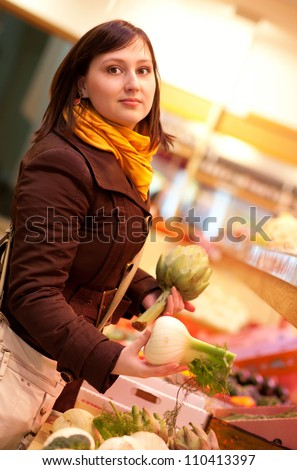 Beautiful young woman buying artichokes and fennel bulbs at market