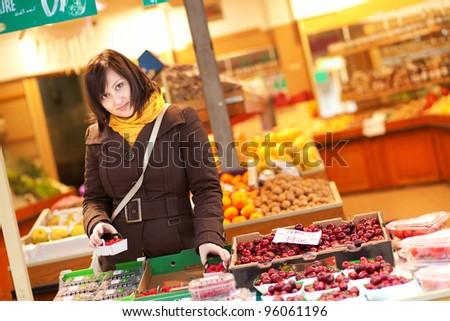 Beautiful young woman buying fruits at market