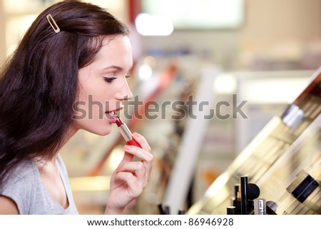 Beautiful young woman buying lipstick. Shallow DOF.
