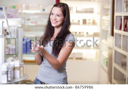 Beautiful young woman buying perfume. Shallow DOF.