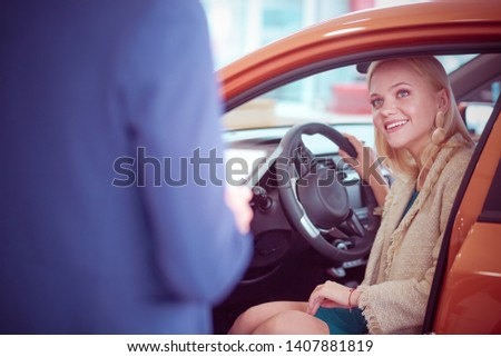 Beautiful young woman buys a car in the dealership saloon