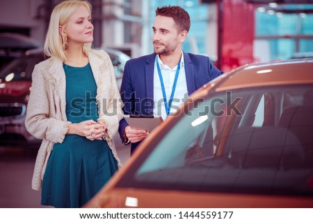 Beautiful young woman buys a car in the dealership saloon #1444559177