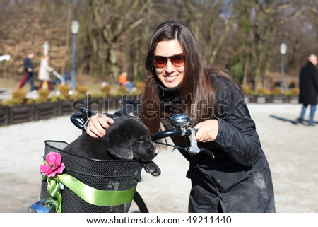 Beautiful young woman carrying little puppy in her bicycle basket carrier