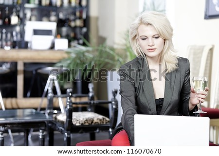 Beautiful young woman chatting with friends on her laptop while enjoying a glass of wine in a bar - stock photo