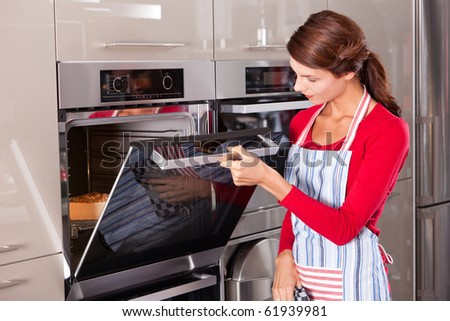 Beautiful young woman checking how her cake is doing in the oven