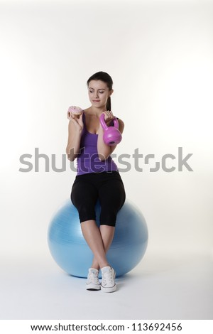 Beautiful Young Woman choosing if she should work out on her gym ball and weights or eat a nice unhealthy cake