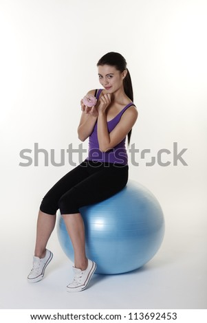 Beautiful Young Woman choosing if she should work out on her gym ball or eat a nice unhealthy cake