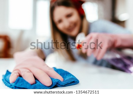 Beautiful young woman cleaning house with microfiber rag. Housekeeping concept. #1354672511