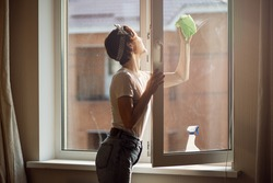 Beautiful young woman cleaning window at home.