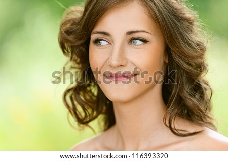 Beautiful young woman close-up, against green of summer park. - stock photo