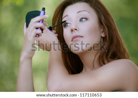 Beautiful young woman close-up colors lashes mascara, against background of summer green park.