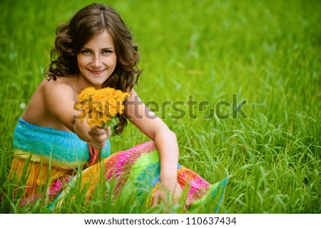 Beautiful young woman close-up in colorful dress sitting on grass with bouquet of yellow flowers, against green of summer park.