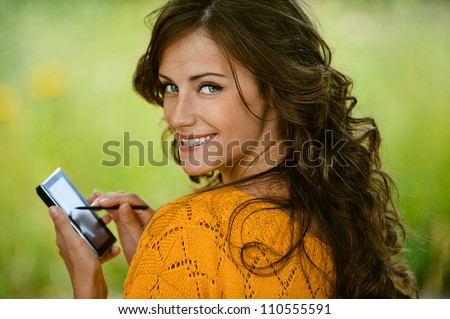 Beautiful young woman close-up in orange sweater is typing with stylus on device, against green of summer park.