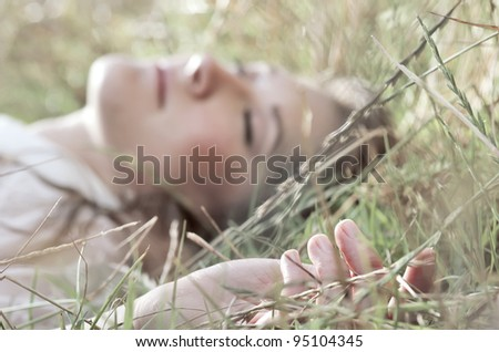 Beautiful young woman closes her eyes while enjoying the sun shining on her, selective focus on her hand