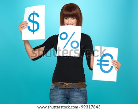 beautiful, young woman comparing a dollar, an euro and a percent sign on three pieces of paper, on blue background