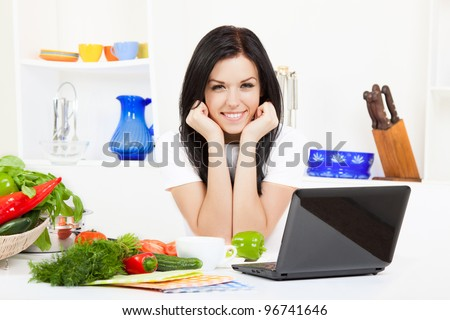 Beautiful young woman cooking looking at camera happy smile, laptop with receipt in the kitchen