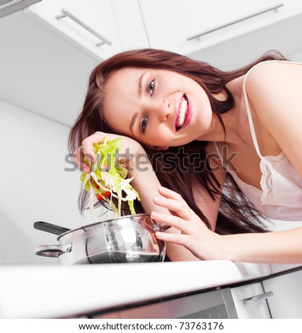 beautiful young woman cooking soup in the kitchen