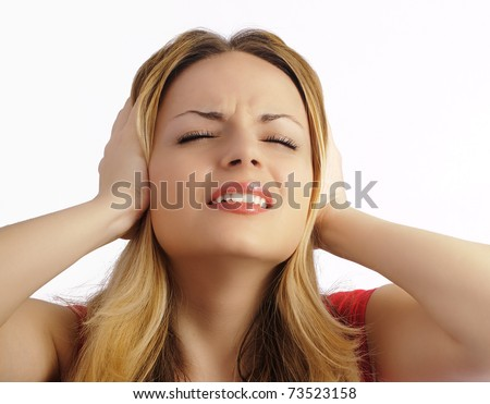 Beautiful young woman covering her ears with her hands, blocking out the noise or having a headache