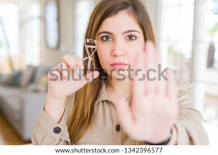 Beautiful young woman curling eyelashes using eyelash curler with open hand doing stop sign with serious and confident expression, defense gesture