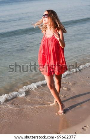 beautiful young woman dancing on the beach