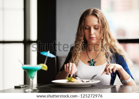 Beautiful young woman dining at a restaurant - stock photo