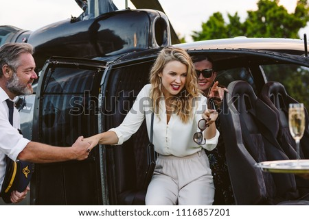 Beautiful young woman disembarking a helicopter with pilot supporting her. Gorgeous young women travelling a helicopter.