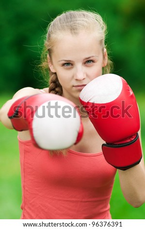 Beautiful young woman doing box exercise in red gloves at green park. Boxer