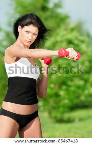 Beautiful young woman doing exercise with dumbbell in green park. Summer