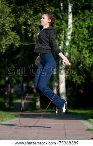 Beautiful young woman doing  exercise with skipping rope at park. Jumping