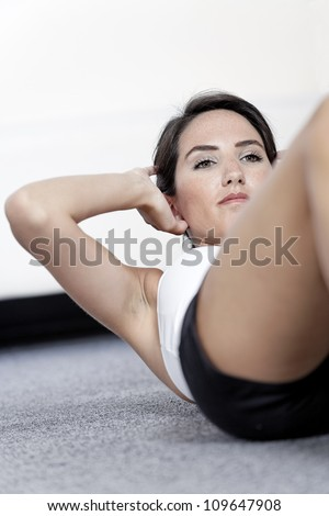 Beautiful young woman doing sit ups at home on the floor