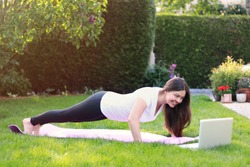 Beautiful young woman doing sport in her garden outdoors following guide of online tutorial or trainer on laptop. Healthy lifestyle. Exercising at home. Doing fitness online
