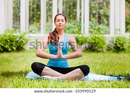 Beautiful young woman doing stretching exercise on green grass at park.