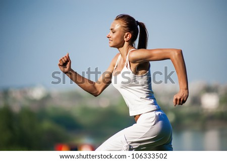 Beautiful young woman doing stretching exercise on green grass at park