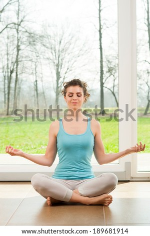 Beautiful young woman doing yoga exercise in her house in front of the big window with a nature view
