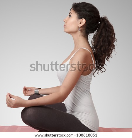 Beautiful young woman doing yoga exercise on mat