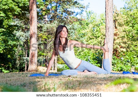 Beautiful young woman doing  yoga exercising on the grass in forest