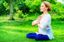 Beautiful young woman doing yoga in the summer park. Healthy lifestyle. Yoga. Lotus pose.