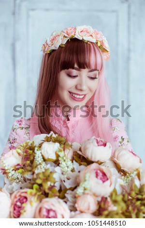 Stock Photo Beautiful young woman doll in a pink dress, in a bright room and flowers, lolita. Japanese street fashion. Portrait.