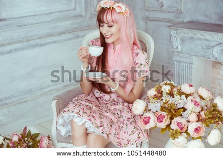 Stock Photo Beautiful young woman doll in a pink dress, in a bright room and flowers sitting in a chair with a cup, tea party, lolita. Japanese street fashion. Portrait.