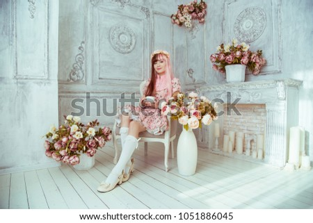 Stock Photo Beautiful young woman doll in a pink dress, in a bright room and flowers sitting in a chair with a cup, tea party, lolita. Japanese street fashion.
